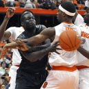 Cincinnati's David Nyarsuk passes the ball under pressure from Syracuse's C.J. Fair, Baye Moussa Keita, right, and Jerami Grant, left, during the first half of an NCAA college basketball game in Syracuse, N.Y., Monday, Jan. 21, 2013. (AP Photo/Kevin Rivoli)