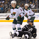 Minnesota Wild center Charlie Coyle (3) and center Mikko Koivu (9), Finland, wait for the puck after checking Los Angeles Kings defenseman Drew Doughty (8) who takes one to the jaw during the first period of an NHL hockey game, Monday, March 31, 2014, in