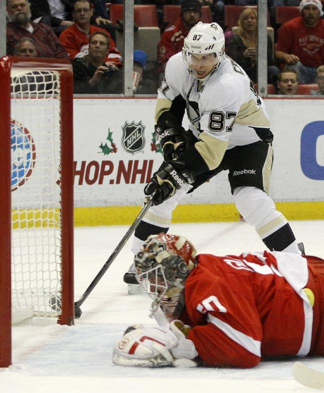 Pittsburgh Penguins' Sidney Crosby (87) works the puck around the goalpost to score against Detroit Red Wings goalie Jonas Gustavsson (50), of Sweden, during the first period of an NHL hockey game on Saturday, Dec. 14, 2013, in Detroit