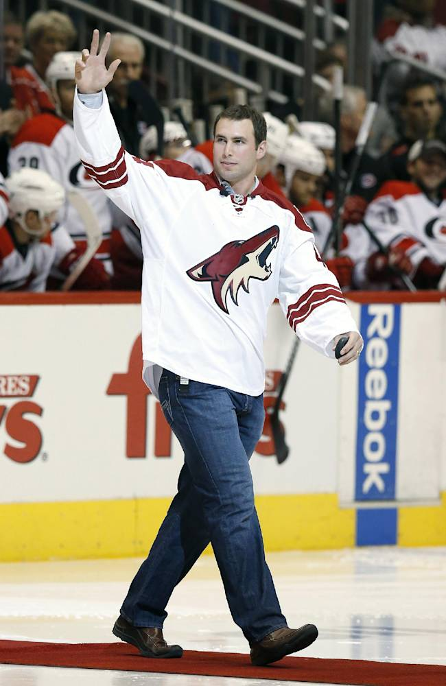 Arizona Diamondbacks first baseman Paul Goldschmidt waves to the crowd before he drops the ceremonial first puck prior to an NHL hockey game between the Phoenix Coyotes and the Carolina Hurricanes, Saturday, Dec. 14, 2013, in Glendale, Ariz