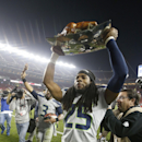 Seattle Seahawks cornerback Richard Sherman (25) carries a turkey off the field as quarterback Russell Wilson (3) waves to fans after the Seahawks beat the San Francisco 49ers 19-3 in an NFL football game in Santa Clara, Calif., Thursday, Nov. 27, 2014 Th