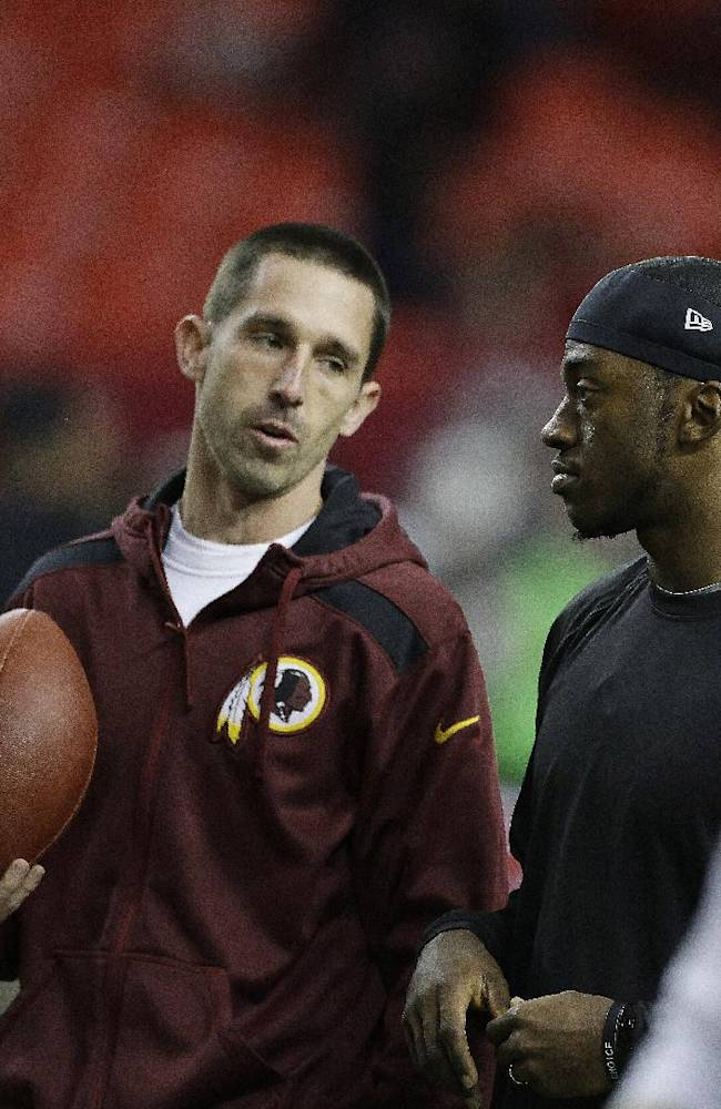 Washington Redskins quarterback Robert Griffin III, right speaks with Washington Redskins offensive coordinator Kyle Shanahan before the first half of an NFL football game against the Atlanta Falcons, Sunday, Dec. 15, 2013, in Atlanta