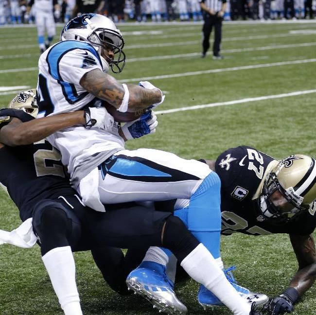 Carolina Panthers wide receiver Steve Smith (89) pulls in a touchdown pass as he is brought down by New Orleans Saints cornerback Keenan Lewis, left, and safety Malcolm Jenkins, right, in the second half of an NFL football game in New Orleans, Sunday, Dec. 8, 2013. The Saints won 31-13
