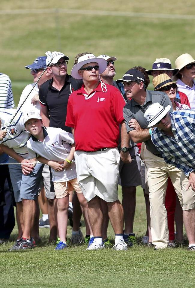 Golf fans watch the ball after Rory McIlroy of Northern Ireland played a fairway shot on the 12th hole during the Australian Open golf tournament in Sydney, Australia, Thursday, Nov. 28, 2013