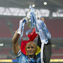 Manchester City captain Manchester City's Vincent Kompany holds up the trophy as he celebrates after his team's 3-1 win against Sunderland in the League Cup Final at Wembley Stadium, London, England, Sunday March 2, 2014