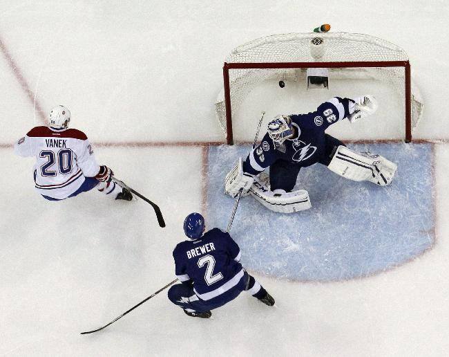 Montreal Canadiens left wing Thomas Vanek (20), of Austria, scores past Tampa Bay Lightning goalie Anders Lindback (39), of Sweden, and defenseman Eric Brewer (2) during the third period of Game 1 of a first-round NHL hockey playoff series on Wednesday, April 16, 2014, in Tampa, Fla