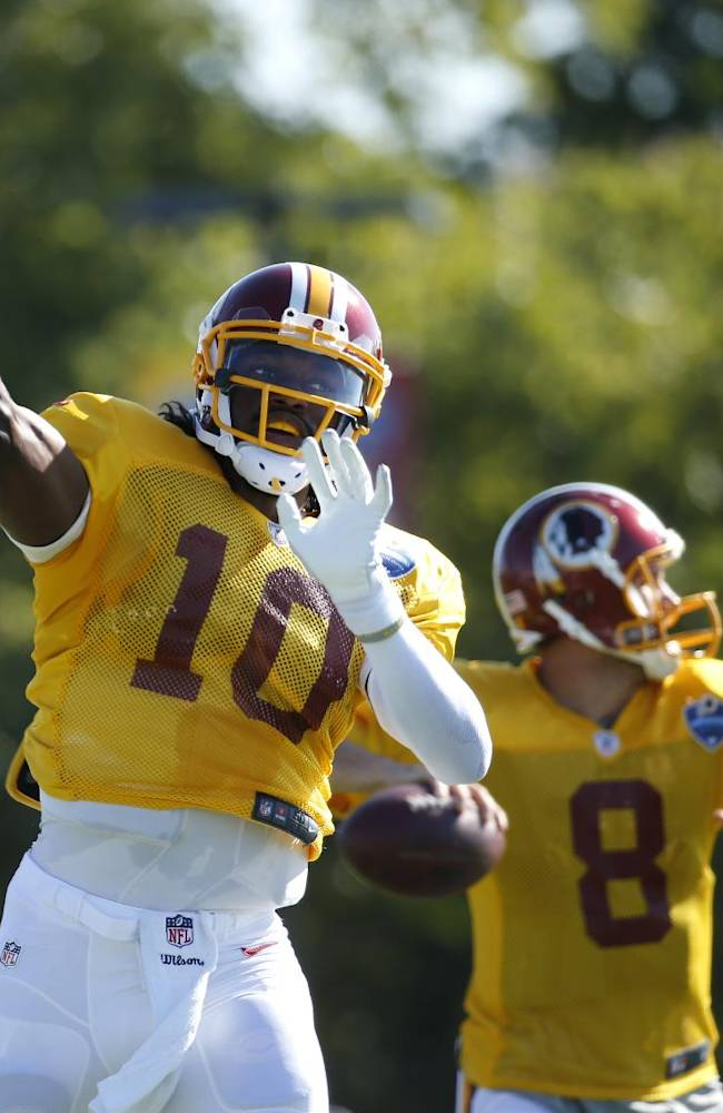 Washington Redskins quarterbacks Robert Griffin III, left, and Kirk Cousins throw during practice at the team's NFL football training facility, Monday, July 28, 2014 in Richmond, Va