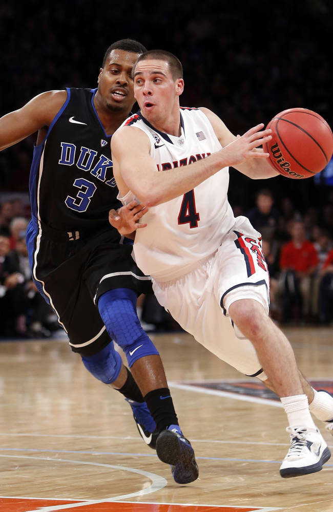This Nov. 29, 2013 file photo shows Arizona's T.J. McConnell (4) driving against Duke's Tyler Thornton (3) during the first half of an NCAA college basketball game in the championship of the NIT Season Tip-off tournament in New York
