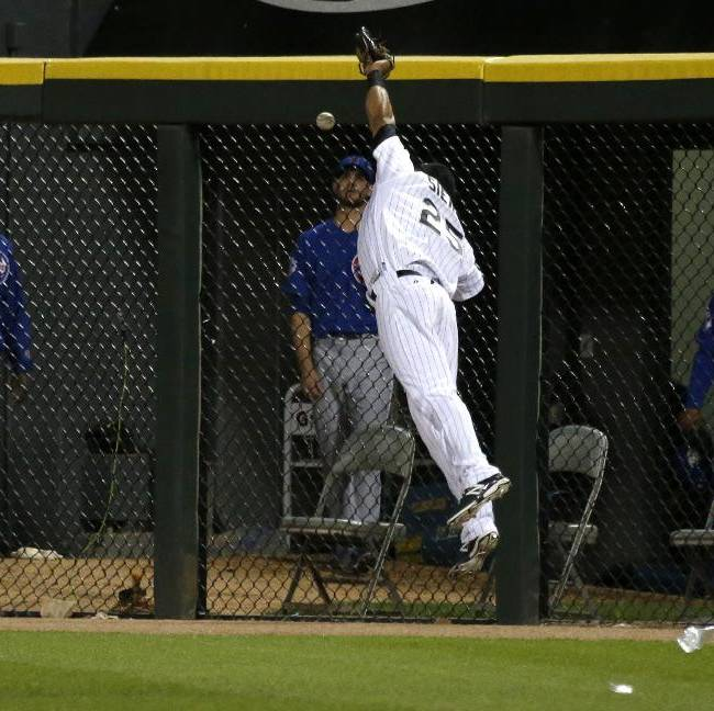 Chicago White Sox right fielder Moises Sierra is unable to catch a long fly ball off the bat of Chicago Cubs' Anthony Rizzo during the eighth inning of an interleague baseball game Thursday, May 8, 2014, in Chicago