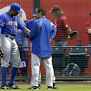 New York Mets' Curtis Granderson (3) is looked at by Mets training staff after Granderson tried to make a play on a ball hit by Arizona Diamondbacks' Miguel Montero in the first inning of a baseball game on Monday, April 14, 2014, in Phoenix. Granderson