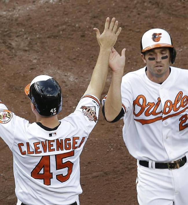 Baltimore Orioles' Steve Clevenger, left, and J.J. Hardy high-five after scoring on a single by Ryan Flaherty in the fifth inning of the first baseball game of a doubleheader against the Pittsburgh Pirates, Thursday, May 1, 2014, in Baltimore