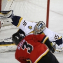 Nashville Predators goalie Pekka Rinne, of Finland, stops a shot by Calgary Flames' Ladislav Smid, of the Czech Republic, during the first period of an NHL hockey game in Calgary, Alberta, Friday, March 21, 2014 The Associated Press