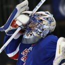 New York Rangers goalie Henrik Lundqvist adjusts his mask after giving up a goal to the Tampa Bay Lightning during the third period of Game 2 of the Eastern Conference final during the NHL hockey Stanley Cup playoffs, Monday, May 18, 2015, in New York. (AP Photo/Kathy Willens)