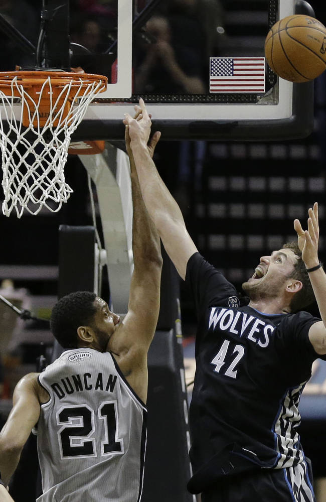 San Antonio Spurs' Tim Duncan (21) and Minnesota Timberwolves' Kevin Love (42) compete for a rebound during the first half on an NBA basketball game, Sunday, Jan. 12, 2014, in San Antonio. San Antonio won 104-86
