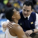 Michigan guard Trey Burke (3) is checked by a trainer after falling to the court in the second half of a second-round game against South Dakota State in the NCAA college basketball tournament Thursday, March 21, 2013, in Auburn Hills, Mich. (AP Photo/Duane Burleson)