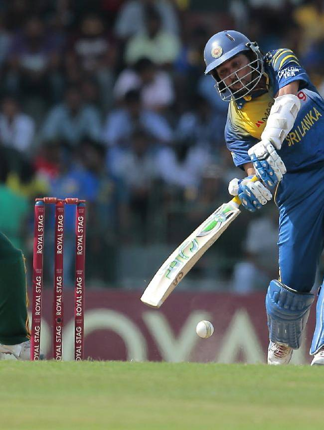 Sri Lankan batsman Tillakarathne Dilshan plays a shot in front of South African wicket keeper Quinton de Cock during the first one-day international cricket match between Sri Lanka and South Africa in Colombo, Sri Lanka, Sunday, July 6, 2014