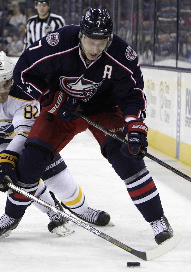 Columbus Blue Jackets' Jack Johnson, right, tries to control the puck as Buffalo Sabres' Marcus Foligno defends during the second period of an NHL hockey game, Saturday, Jan. 25, 2014, in Columbus, Ohio