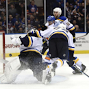 New York Islanders center John Tavares, partly hidden, shoots the puck pas St. Louis Blues goalie Martin Brodeur (30) and right wing T.J. Oshie (74) to score in the second period of an NHL hockey game at Nassau Coliseum on Saturday, Dec. 6, 2014, in Union