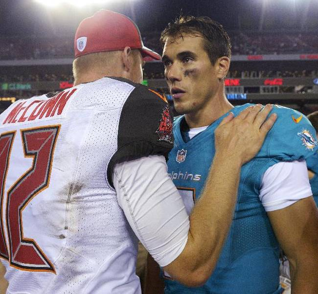 Tampa Bay Buccaneers quarterback Josh McCown (12) congratulates Miami Dolphins quarterback Brady Quinn after the Dolphins defeated the Buccaneers 20-14 during an NFL preseason football game Saturday, Aug. 16, 2014, in Tampa, Fla