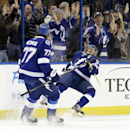 Tampa Bay Lightning right wing Martin St. Louis, right, falls down as he celebrates with defenseman Victor Hedman, of Sweden, after St. Louis scored against the New York Rangers during the first period of an NHL hockey game Monday, Nov. 25, 2013, in Tampa