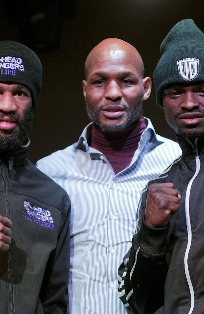 IBF junior welterweight champion Lamont Peterson, left, and a Canada's Dierry Jean, right, pose with pose with Bernard Hopkins, center, from Golden Boy Promotion, during a boxing news conference, Thursday, Jan. 23, 2014 in Washington. Peterson is slated to defend his title against Jean on Saturday at the DC Armory