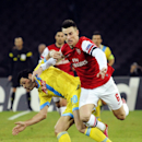 Napoli's Blerim Dzemaili, left, vies for the ball Arsenal Laurent Koscielny during a Champions League, group F, soccer match between Napoli and Arsenal, at the Naples San Paolo stadium, Italy, Wednesday, Dec. 11, 2013