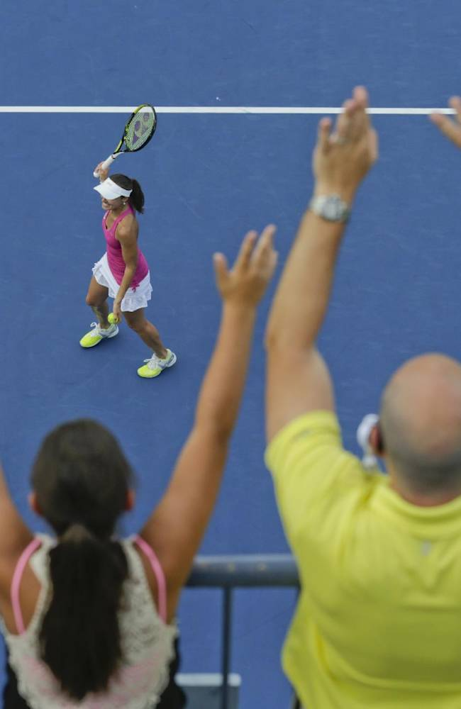 Spectators cheer as Martina Hingis, of Switzerland, prepares to hit autographed balls into the crowd after winning a doubles match with Flavia Pennetta, of Italy, against Kveta Peschke and Katarina Srebotnik in the quarterfinals of the 2014 U.S. Open tennis tournament, Tuesday, Sept. 2, 2014, in New York
