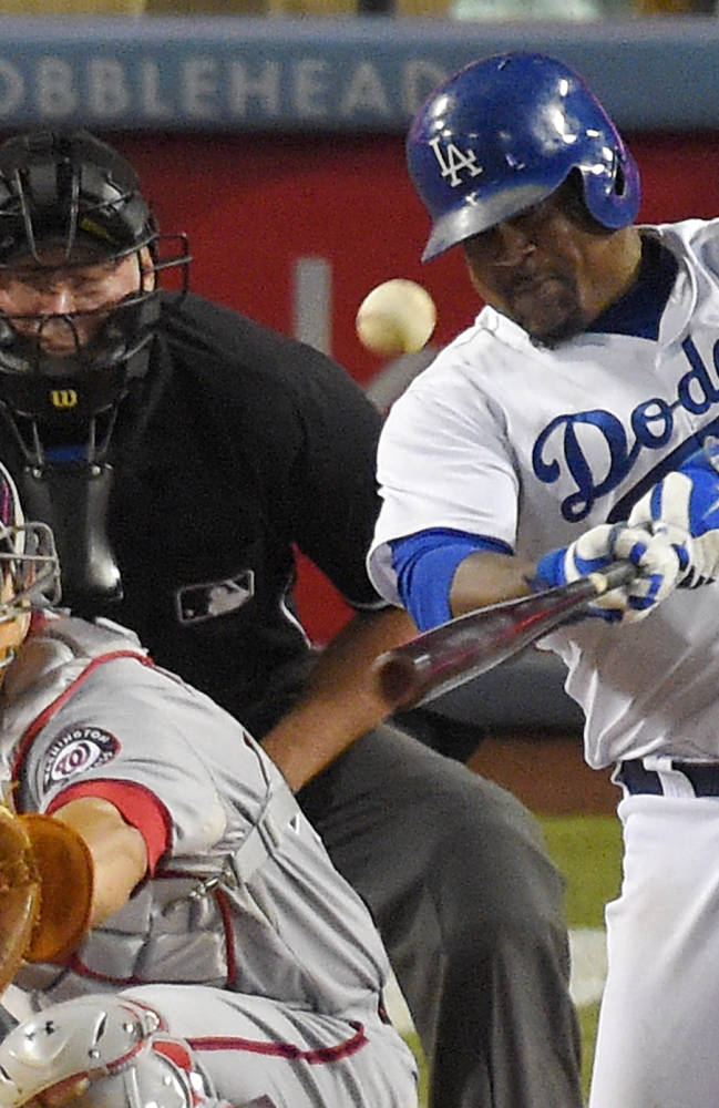 Los Angeles Dodgers' Juan Uribe, right, hits a two-run home run in front of Washington Nationals catcher Wilson Ramos and home plate umpire Ted Barrett during the sixth inning of a baseball game, Tuesday, Sept. 2, 2014, in Los Angeles. (AP Photo/Mark J. Terrill)
