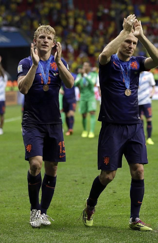 Netherlands' Dirk Kuyt, second left, and Arjen Robben applaud their supporters after their 3-0 victory over Brazil during the World Cup third-place soccer match between Brazil and the Netherlands at the Estadio Nacional in Brasilia, Brazil, Saturday, July 12, 2014