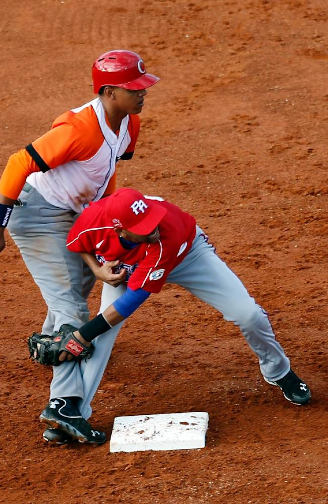 Cuba infielder Ramon Armenteros, left, is tagged out by Puerto Rico infielder Rey Navarro at second base in their Caribbean Series baseball game in Porlamar, Venezuela, Tuesday, Feb. 4, 2014
