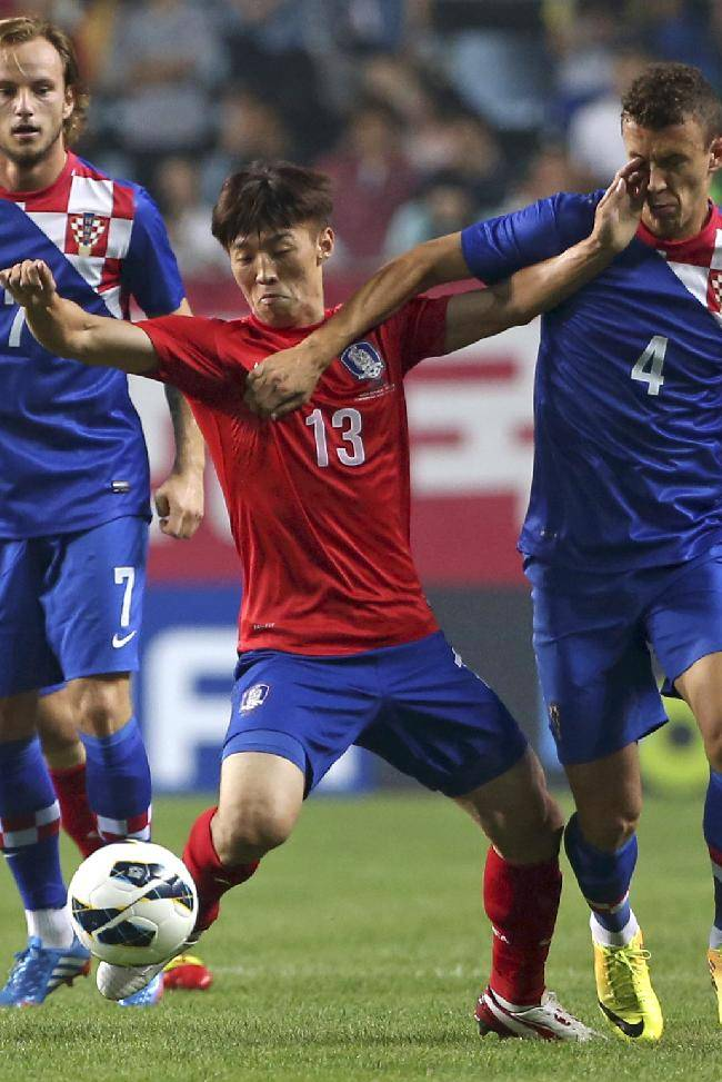 Croatia's Ivan Perisic, right, fights for the ball against South Korea's Kim Bo-kyung as Croatia's Ivan Rakitic , left, looks on during their friendly soccer match at Jeonju World Cup stadium in Jeonju, south of Seoul, South Korea, Tuesday, Sept. 10, 2013. Croatia won the match 2-1