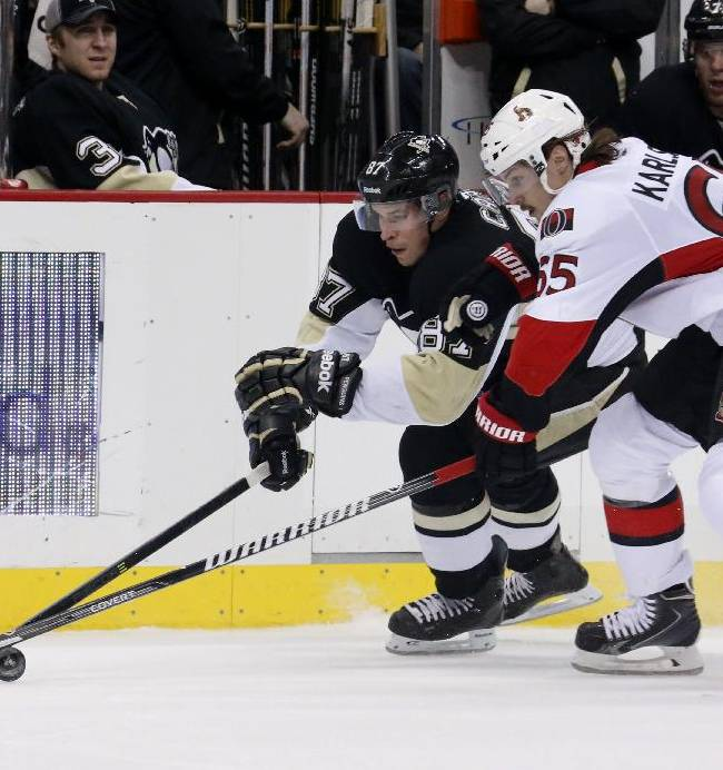 Pittsburgh Penguins' Sidney Crosby, left, battles for the puck against Ottawa Senators' Erik Karlsson (65) in the second period of an NHL hockey game in Pittsburgh, Monday, Feb. 3, 2014
