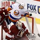 Phoenix Coyotes' Mike Smith (41) makes a save as New York Islanders' Matt Martin (17) collides with Smith during the second period of an NHL hockey game Thursday, Dec. 12, 2013, in Glendale, Ariz. (AP Photo/Ross D. Franklin)