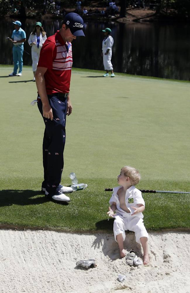 Webb Simpson looks at his son James after he removed his shoes in a bunker during the par three competition at the Masters golf tournament Wednesday, April 9, 2014, in Augusta, Ga