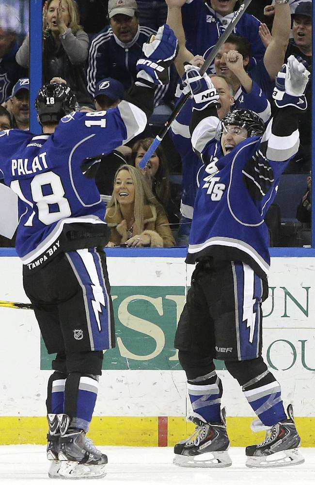 Tampa Bay Lightning center Tyler Johnson (9) celebrates with teammate Ondrej Palat (18), of the Czech Republic, after scoring his third goal of the game against the Colorado Avalanche during the third period of an NHL hockey game Saturday, Jan. 25, 2014, in Tampa, Fla