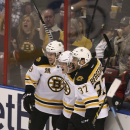 Boston Bruins' Reilly Smith (18) and Patrice Bergeron (37) celebrate with Torey Krug (47) after Krug scored against the Florida Panthers during the third period of an NHL hockey game in Sunrise, Fla., Sunday, March 9, 2014. Boston won 5-2 The Associated