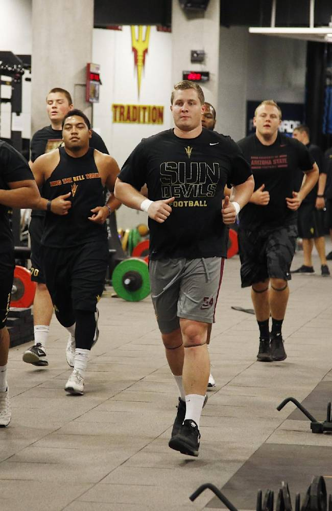 Arizona State football players run between workout stations at the football weight training room on Monday, July 21, 2014, in Tempe, Ariz