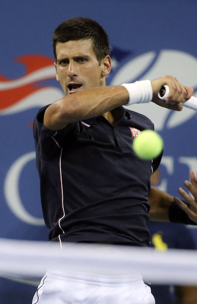 Novak Djokovic, of Serbia, returns a shot to Andy Murray, of Britain, during the quarterfinals of the U.S. Open tennis tournament, Wednesday, Sept. 3, 2014, in New York