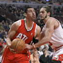 In this Feb. 11, 2014 file photo, Atlanta Hawks forward Gustavo Ayon (14), of Mexico, looks to the basket as Chicago Bulls center Joakim Noah (13) defends during the first half of an NBA basketball game in Chicago. Ayon will miss the remainder of the sea