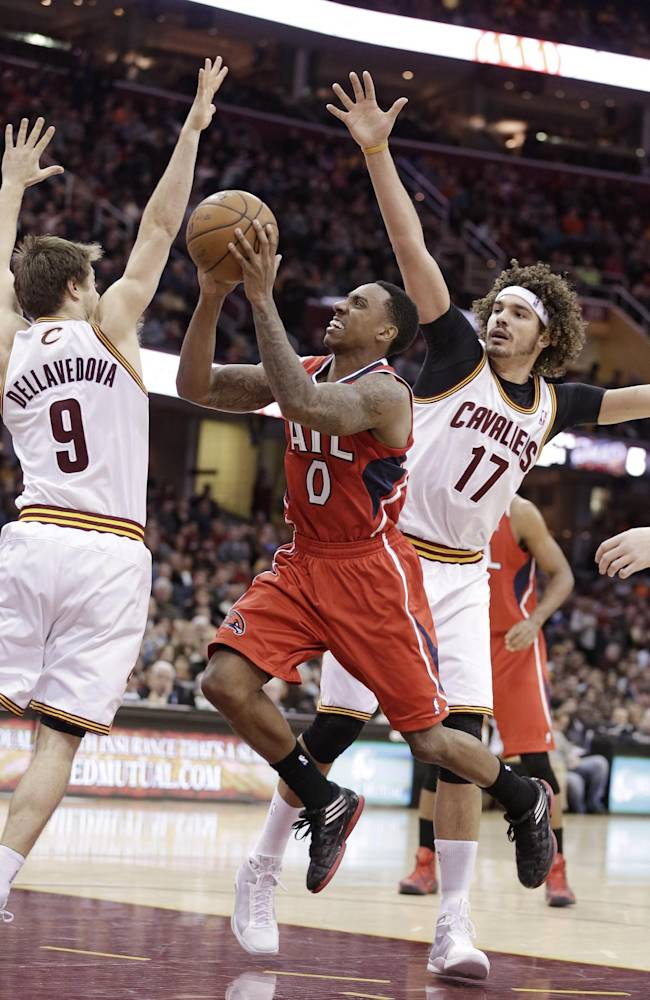 Atlanta Hawks' Jeff Teague (0) jumps to the basket against Cleveland Cavaliers' Matthew Dellavedova (9), from Australia, and Anderson Varejao, from Brazil, during the third quarter of an NBA basketball game Thursday, Dec. 26, 2013, in Cleveland. Atlanta won 127-125 in double overtime