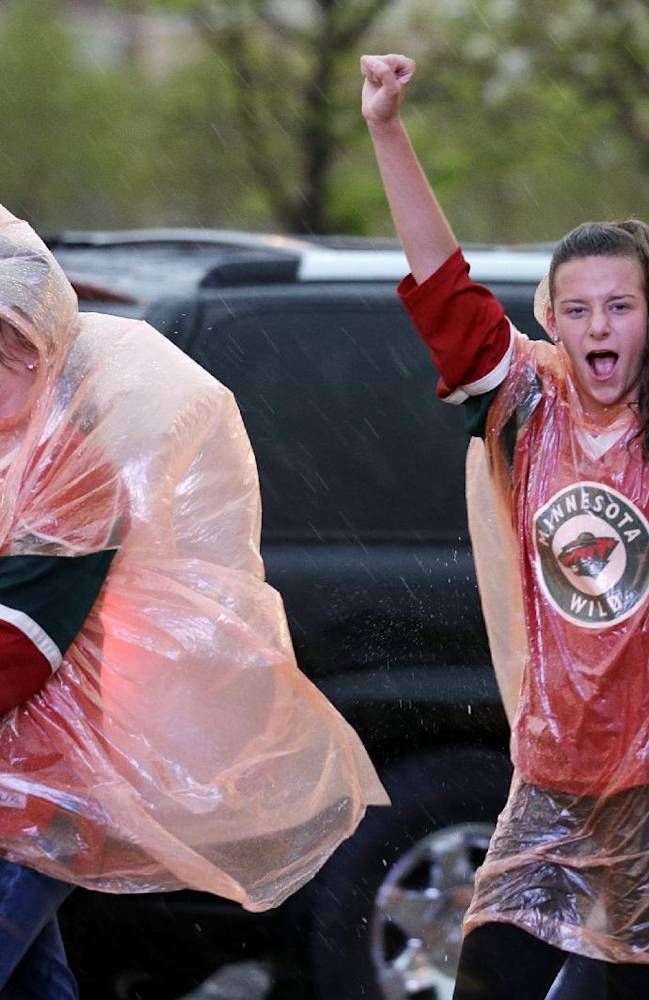Minnesota Wild fans cheer as they walk to the  United Center before Chicago Blackhawks play Minnesota Wild in Game 5 of an NHL hockey second-round playoff series in Chicago,Sunday, May 11, 2014. Thunderstorm warnings were declared for areas including Chicago, as well as Lake, McHenry, DuPage and Kane counties