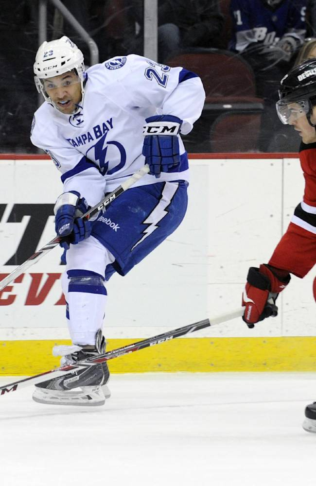 Tampa Bay Lightning right wing J.T. Brown, left, passes the puck past New Jersey Devils' Eric Gelinas during the first period of an NHL hockey game, Saturday, Dec. 14, 2013, in Newark, N.J