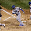 Los Angeles Dodgers' Alex Guerrero, center, celebrates his grand slam with teammates Jimmy Rollins, left, and Chris Heisey in the ninth inning off Colorado Rockies relief pitcher Rafael Betancourt in Game 2 of a baseball doubleheader Tuesday, June 2, 2015, in Denver. (AP Photo/David Zalubowski)