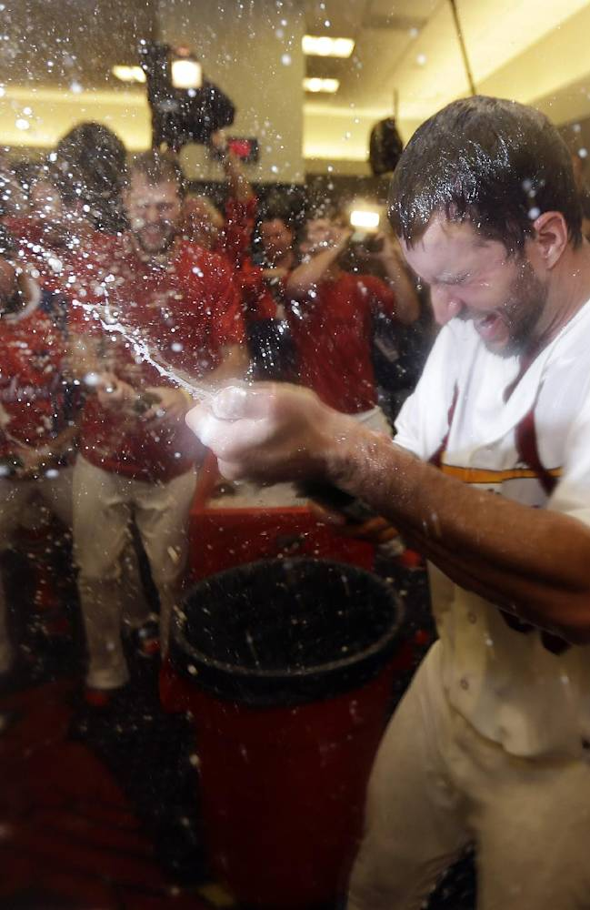 St. Louis Cardinals pitcher Adam Wainwright, right, sprays teammates in the locker room after the Cardinals defeated the Pittsburgh Pirates 6-1 in Game 5 in a National League baseball division series, Wednesday, Oct. 9, 2013, in St. Louis. The Cardinals advanced to the NL championship series against the Los Angeles Dodgers