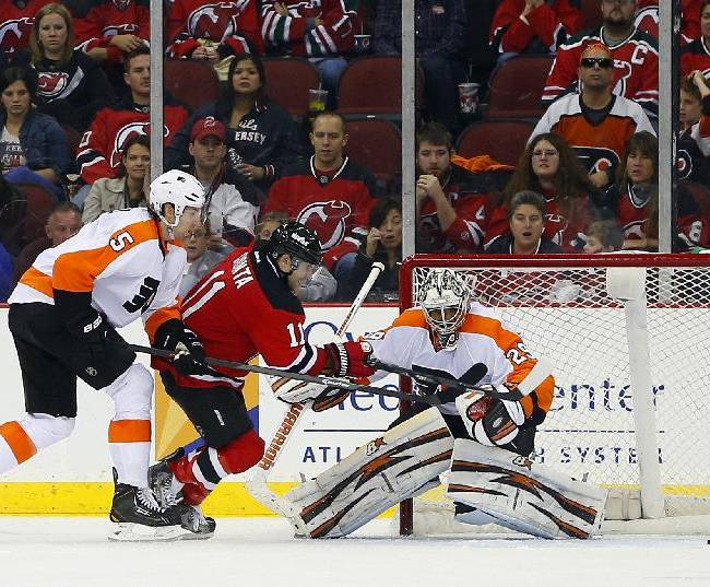 New Jersey Devils' Stephen Gionta (11) fights off Philadelphia Flyers' Braydon Coburn (5) as his shot slide past Flyers goalie Ray Emery during the third period of an NHL hockey game in Newark, N.J., Saturday, Nov. 2, 2013. The Flyers won 1-0