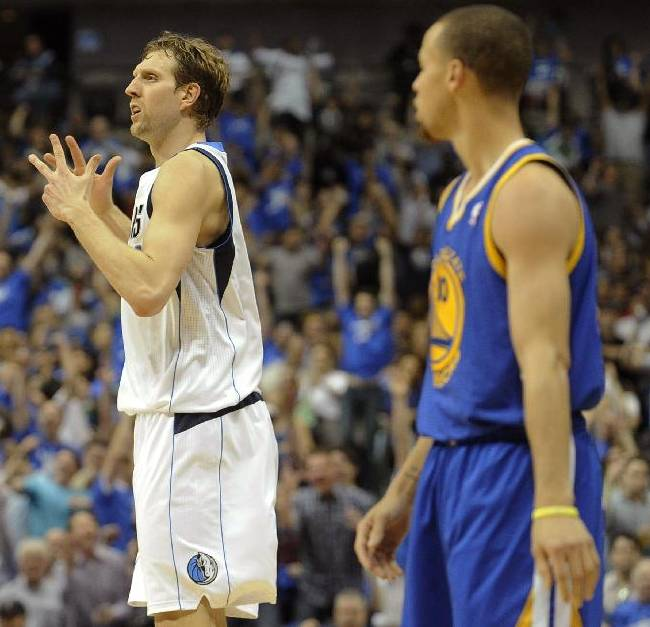 Dallas Mavericks forward Dirk Nowitzki (41) celebrates after a basket as Golden State Warriors guard Stephen Curry (30) looks on in the first half of an NBA basketball game, Tuesday, April 1, 2014, in Dallas