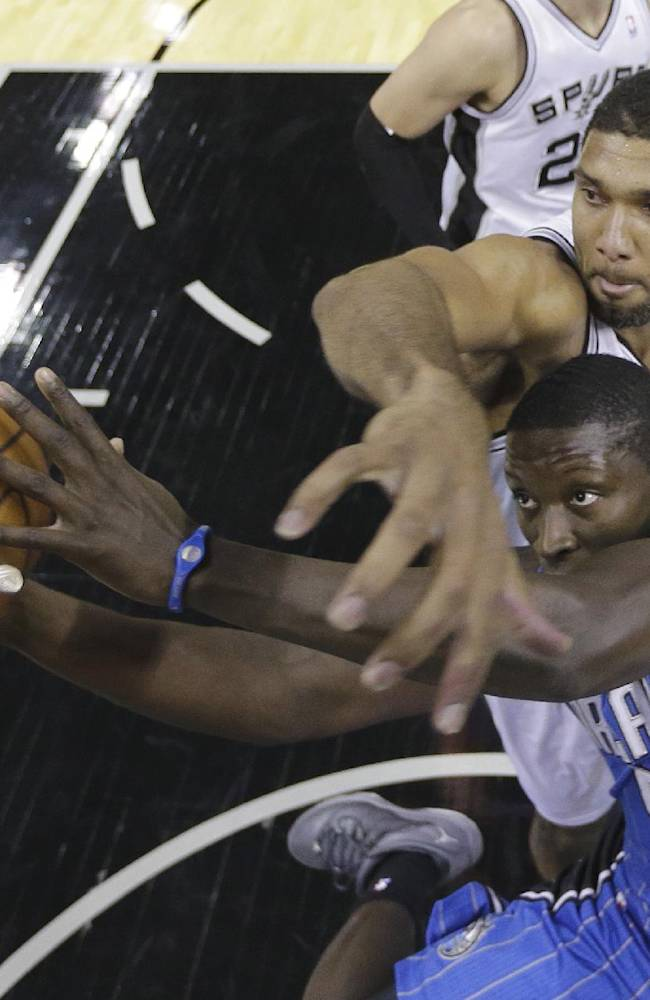 Orlando Magic's Victor Oladipo (5) is defended by San Antonio Spurs' Tim Duncan as he drives to the basket during the first half of a preseason NBA basketball game, Tuesday, Oct. 22, 2013, in San Antonio