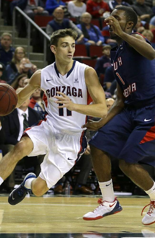 Gonzaga's David Stockton (11) dribbles around South Alabama's Ken Williams, right, in the first half of an NCAA college basketball game, Saturday, Dec. 14, 2013, in Seattle