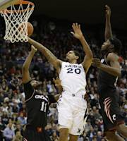 Xavier forward Justin Martin (20) drives between Cincinnati forward Jermaine Lawrence (11) and forward Justin Jackson in the first half of an NCAA college basketball game, Saturday, Dec. 14, 2013, in Cincinnati. (AP Photo/Al Behrman)