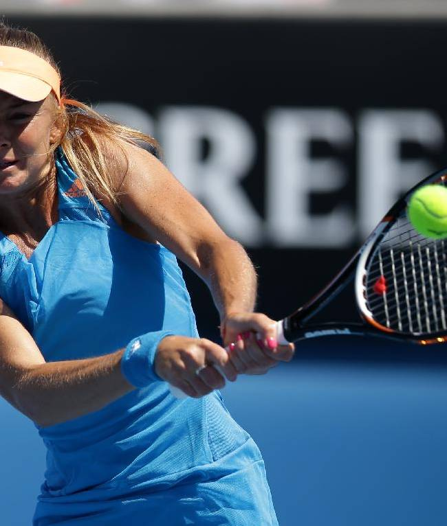Daniela Hantuchova of Slovakia makes a backhand return to Heather Watson of Britain during their first round match at the Australian Open tennis championship in Melbourne, Australia, Monday, Jan. 13, 2014